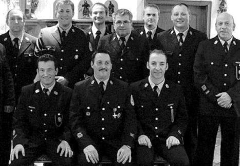 Martin Thoma (vorne, rechts) ist neuer Kommandant der Feuerwehr. Ihm zur Seite steht Hubert Treml (vorne, links). In der Mitte sitzt der alte Kommandant Reinhold Suttner. Mit im Bild: Vorsitzender Rudi Kreuzer (stehend, Vierter von links) und zweiter Vorsitzender Erich Beer (stehend, zweiter von rechts). Bild: lng